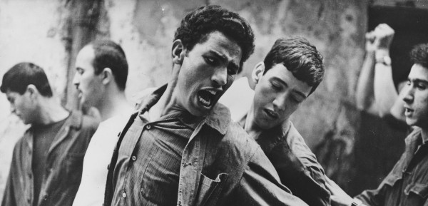 Brahim Haggiag (center, with arm outstretched) as revolutionary leader Ali La Pointe in a scene from Gillo Pontecorvo's THE BATTLE OF ALGIERS (1965). Photo courtesy Rialto Pictures.